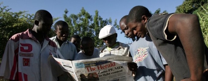 Zimbabweans reading a newspaper copy